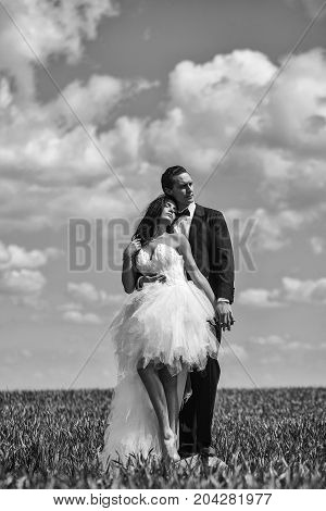 young wedding couple of sexy girl with brunette hair and pretty face in white bride dress and handsome man in black groom suit on green grass in field on cloudy blue sky natural background