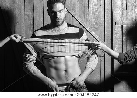 One sexual young stylish handsome muscular lover macho man with beard in sweater with bare torso and female mistress hand undressing him standing indoor in studio on wooden backdrop horizontal photo