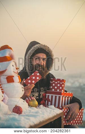 Happy Hipster With Present Boxes On Snowy Landscape