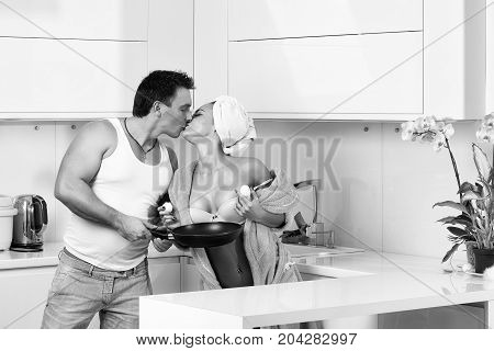 Sexy young family kissing couple of woman in blue terry dressing gown and towel turban on head and muscular handsome man undressing her standing in kitchen cooking breakfast horizontal picture