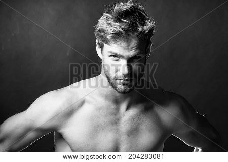 Closeup view portrait of one handsome young muscular naked sexy macho man with short hair bare chest abd beautiful body standing in studio on black backdrop horizontal picture