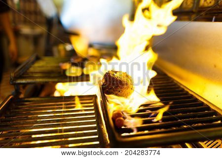The side photo of the raw meat grilling on the brazier with burning wood