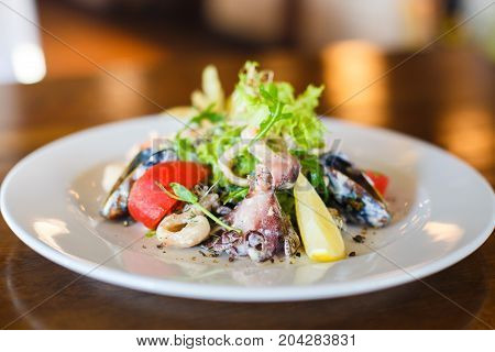 The close-up side view of the salad made of the seafood such as mussels, octopus, lettuce, tomatoes, lemon and onion circles placed on the white plate