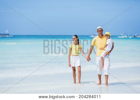 Family of three - father with his child having fun at the white sand beach
