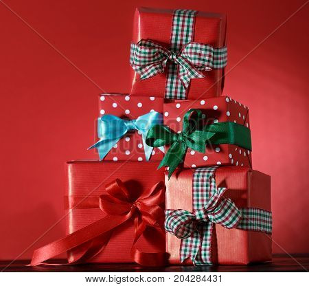 Stack of wrapped red boxed decorated with ribbons and arranged in stack on red background.