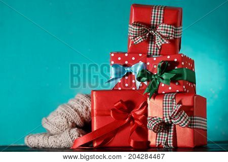 Stack of wrapped red boxed decorated with ribbons and arranged in stack on blue background.