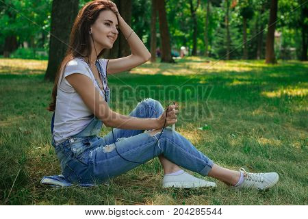 charming pretty girl sitting on the grass in the Park and listens to music with headphones