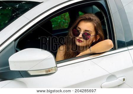 beautiful lady driver in glasses sits by the wheel car