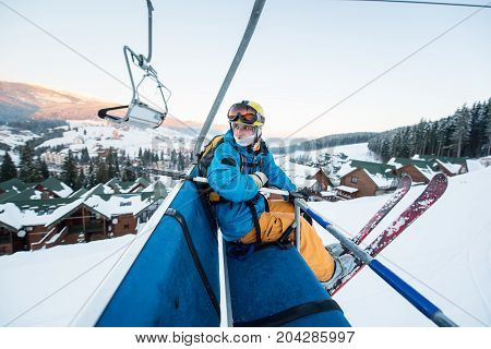 Skier Guy Sitting At Ski Chair Lift In Beautiful Evening At The Winter Resort And Turns Back. Close-