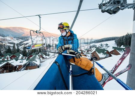 Professional Male Skier Sitting At Ski Chair Lift In The Evening And Turns Back. Close-up. Concept O