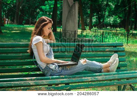 young brunette girl sits on a bench and using a laptop outdoors
