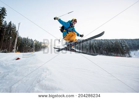 Flying Skier Man At Jump From The Slope Of Mountains Performing A High Jump And Looking Apprehensive