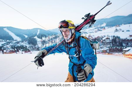 Close-up A Guy Skier In A Blue Jacket, A Yellow Helmet And Glasses Is Holding Sticks On His Shoulder