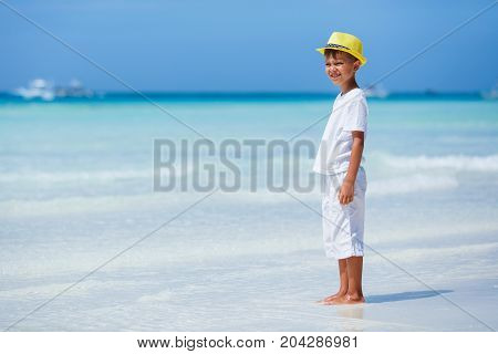 Little boy wearing white having fun on tropical ocean beach. Kid during family sea vacation. Summer water fun.