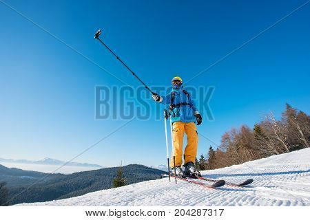 Professional Skier Standing On Top Of A Mountain On A Beautiful Sunny Winter Day Taking A Selfie Wit