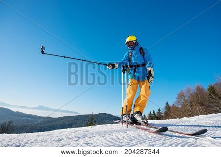 Full Length Shot Of A Skier Standing On Top Of A Mountain On A Beautiful Sunny Winter Day Taking A S
