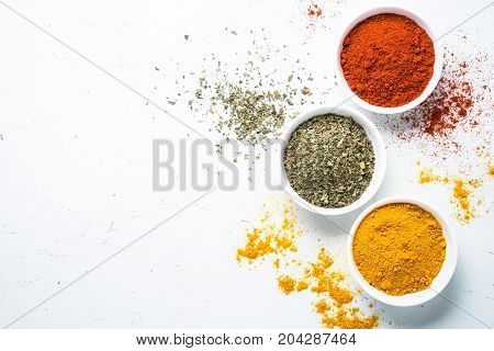 Various spices in a bowls on white background. Red green and yellow spices. Top view.