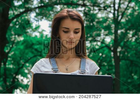 close-up portrait of a serious young Brunettes with a laptop in the Park