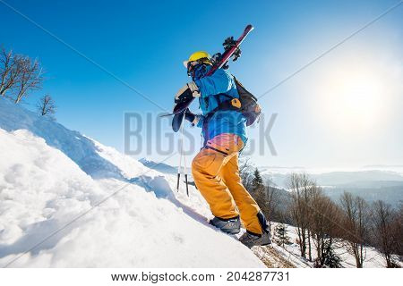 Professional Skier Walking Up The Snowy Hill In The Mountains Carrying His Equipment On A Sunny Day
