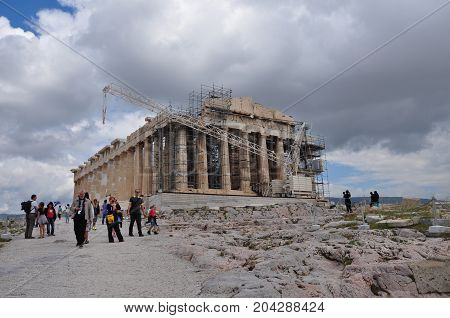 ATHENS GREECE - MAY 6 2014: People visiting the Acropolis and the temple of Parthenon under repairs with crane and scaffold.
