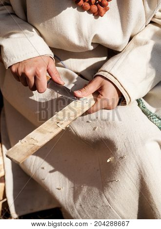 Female Carpenter Hands Holding Knife And Wooden Plank, Vertical