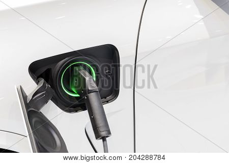 The electric car charger plugged in to the socket.The modern electric car charging the battery