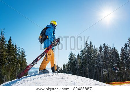 Full Length Shot Of A Skier Walking On The Top Of The Snowy Slope, Carrying His Ski Equipment Copysp