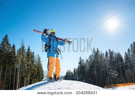 Full Length Shot Of A Skier Standing On Top Of A Snowy Slope In The Mountains, Raising His Arms In T