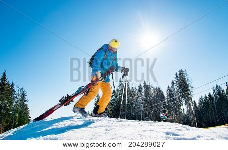 Male Skier Walking Up The Snowy Hill In The Mountains Carrying His Ski Equipment. Beautiful Sunny Wi