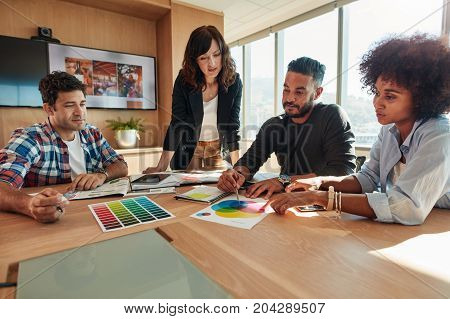 Group of creative designers team discussing project choosing color scheme laying out swatches in conference room.