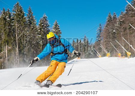 Male Skier Skiing In The Mountains Copyspace Ski Resort. Blue Sky And Winter Forest On The Backgroun