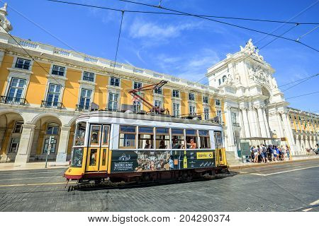 Lisbon, Portugal - August 25, 2017: historic yellow Tram 28 in front of Rua Augusta Triumphal Arch in Commerce Square or Praca do Comercio. Tram 28 and Rua Augusta Arch are popular tourist attractions