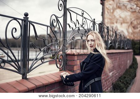 Beautiful woman posing on embankment of the European city next to the forged fence. She is dressed in a coat and her blond hair is fluttering from the wind