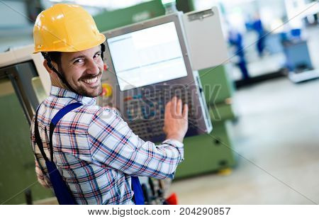 Industry Worker working on cnc machine in metal industry factory