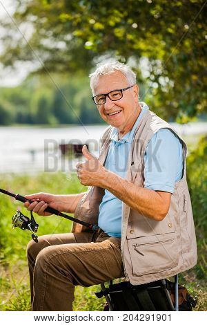 Happy senior man is fishing on sunny day..