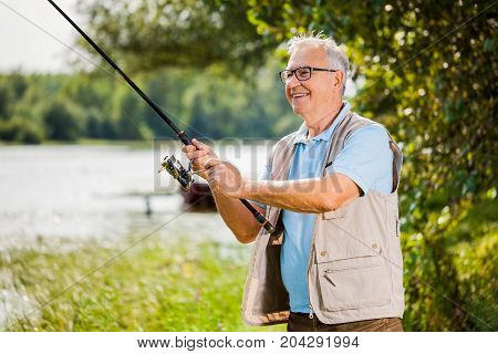 Happy senior man is fishing on sunny day.