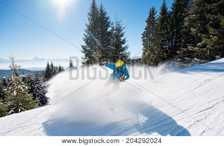 Professional Skier Skiing Downhill In The Carpathians Mountains. Blue Sky And Winter Forest On The B