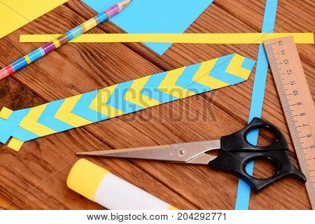 Yellow and blue bookmark from folded paper. Scissors, glue stick, colored paper sheets, ruler, pencil on a desk. Simple paper art projects. Paper craft for children with folding paper
