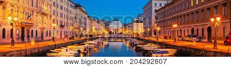 Trieste Italy. Church of St. Antonio Thaumaturgo with Canal Grand in the evening. Sunset sky with boats and illuminated buildings