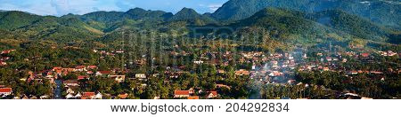 Luang Prabang Laos. Aerial view of Luang Prabang town in Laos. Small touristic city surrounded by mountains. Colorful blue sky