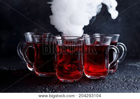 Red Cocktail With Ice Vapor. Red Cold Tea With Steam On A Black Background.