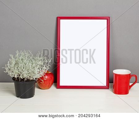 Red frame mockup with plant pot mug and apple on wooden shelf. Empty frame mock up for presentation design. Template framing for modern art.