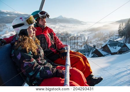 Close-up Of Couple Man And Woman Snowboarders On A Cable Ski Lift In The Morning In Bukovel Enjoying