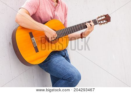 Sound music passion talent concept. Person playing on guitar. Man leaning on wall while playing on instrument