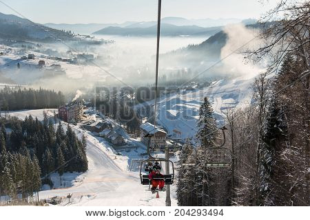 Skiers Riding Up On A Ski Lift At The Winter Ski Resort In Bukovel With An Ideal Landscape Of Snow-c