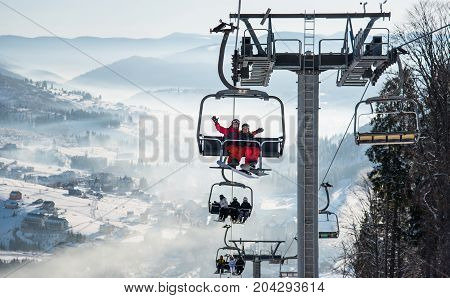Young Couple Snowboarders Riding Up At Ski Lift At Skiing And Snowboarding Winter Resort In The Moun