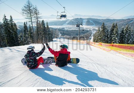 Snowboarders Sit On The Top Of The Ski Slope Under The Ski Lift Let's High Five To Each Other With A