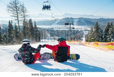 Snowboarders Resting On The Top Of The Ski Slope Under The Ski Lift At Winter Resort With A Beautifu