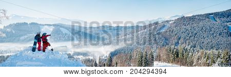 Winter Panorama Of The Mountains Landscape And Forests In A White Haze, Two Snowboarders Resting On