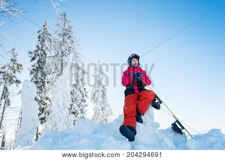 Horizontal Shot Of A Male Snowboarder Resting On Top Of The Mountain With His Snowboard, Observing N